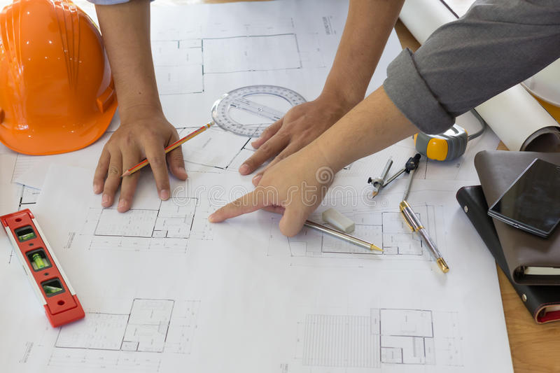 Architect working on blueprint. Architects workplace - architectural project, blueprints, ruler, calculator, laptop and divider co royalty free stock photography