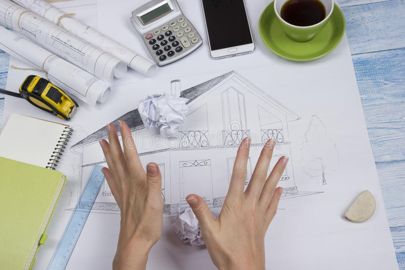 Architect working on blueprint. Architects workplace - architectural project, blueprints, ruler, calculator, laptop and royalty free stock images