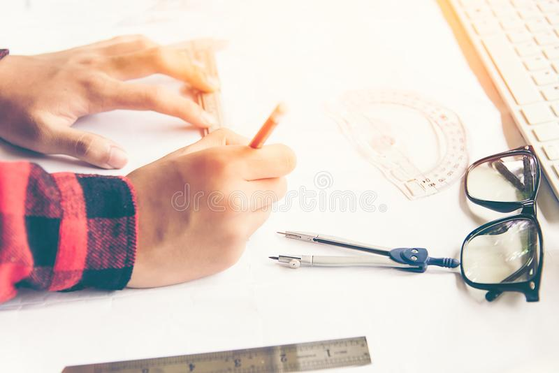 Architect working on blueprint. Architects workplace.Engineer tools and safety control,. Blueprints, ruler,radio,laptop and divider compass.Construction Concept stock photo