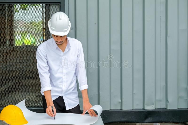 Architect working on blueprint.,engineer inspector in workplace Engineers in helmets planning new project stock images