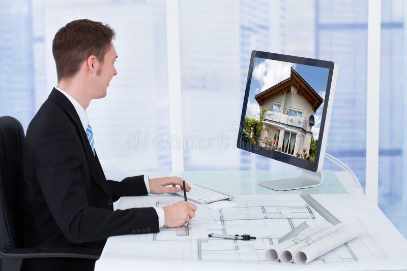 Architect Working On Blueprint terwijl het Bekijken Co royalty-vrije stock foto