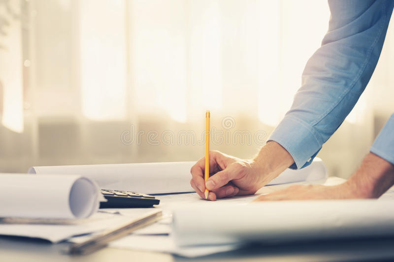 Architect working with blueprints in office stock image
