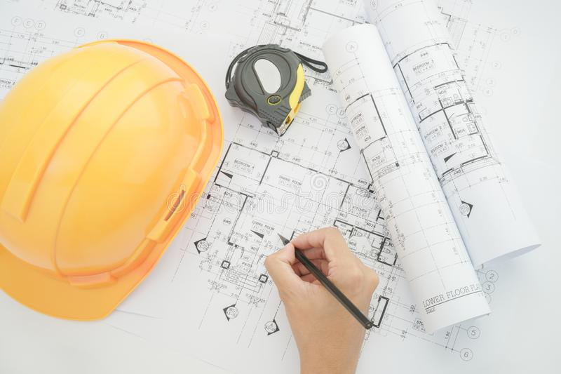 Architect working on construction blueprint. Architects workplace - architectural project, blueprints, helmet, measuring tape. Construction concept stock photo