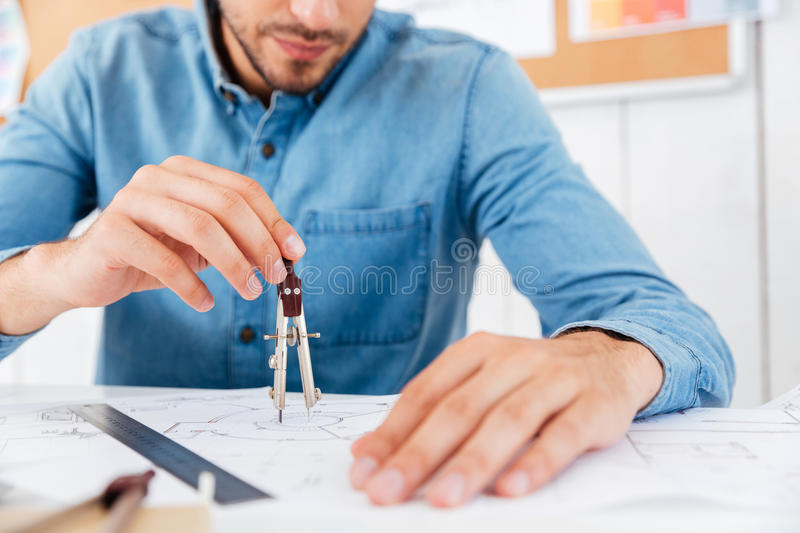 Architect working on construction blueprint in office with divider stock photos