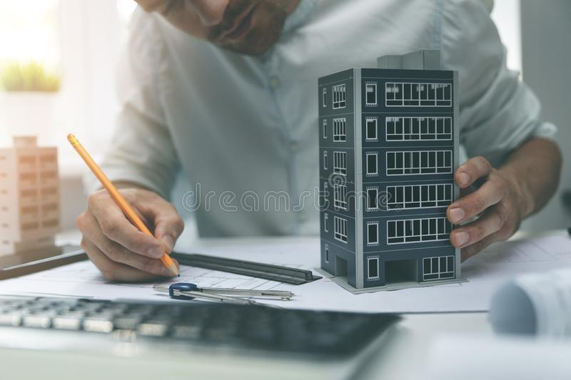 Architect working with new apartment building scale model in office stock photography