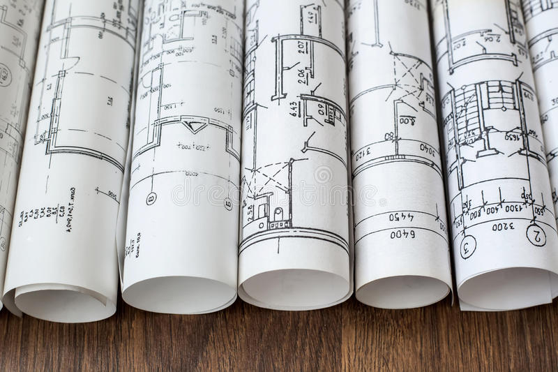 Architect workplace. Architectural project, blueprints, blueprint rolls on wooden desk table. Construction background. stock images