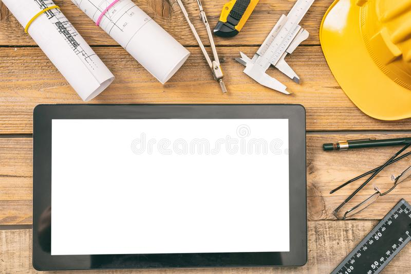 Architect workplace. Tablet with white blank screen, project construction blueprints and engineering tools on wooden desk, copy sp. Architect workplace and stock photos