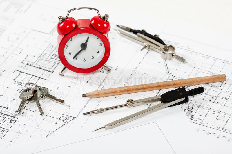 Architect workplace top view. Architectural project, blueprints, calculator, red alarm clock, keys, divider compass and pencil on desk table. Real Estate stock images