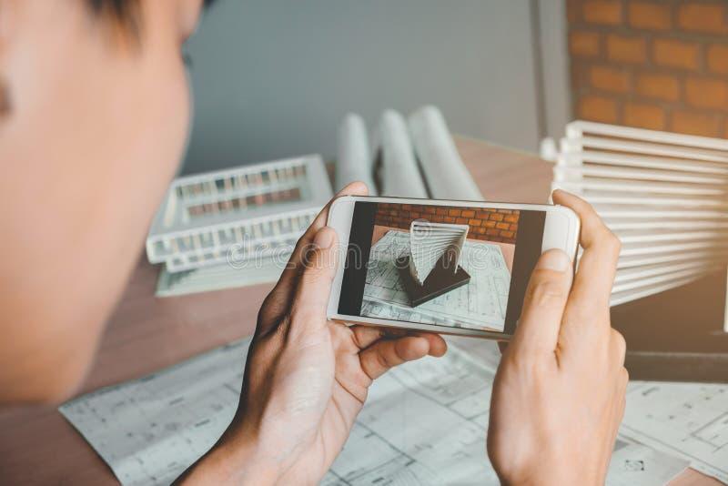 Architecte à l'aide de la création de modèles intelligente de photographie de téléphone dans le bureau image stock