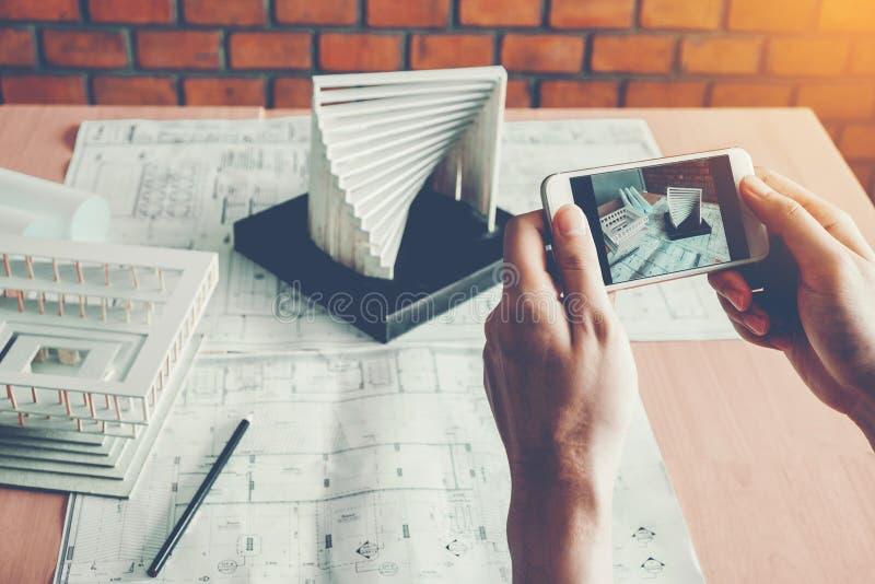 Architecte à l'aide de la création de modèles intelligente de photographie de téléphone dans le bureau photographie stock