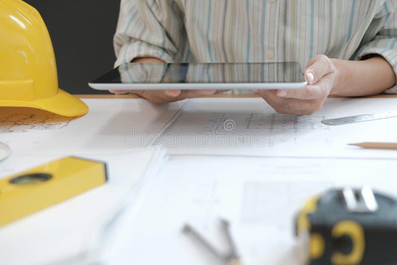 architecte à l'aide du comprimé ingénieur travaillant au modèle de maison de r photos stock
