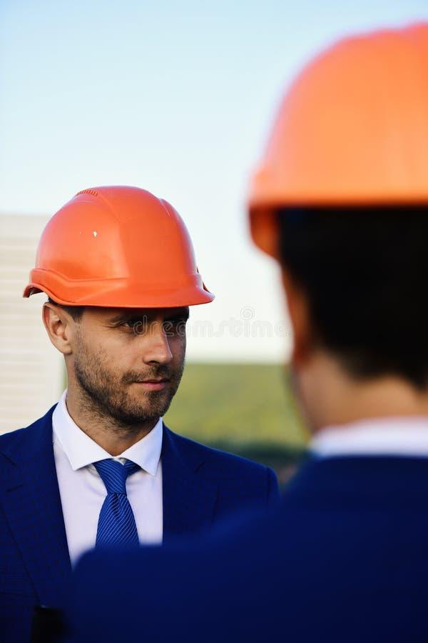 Architecte avec le sourire sûr dans le casque de tenue de soirée et d'orange photo stock