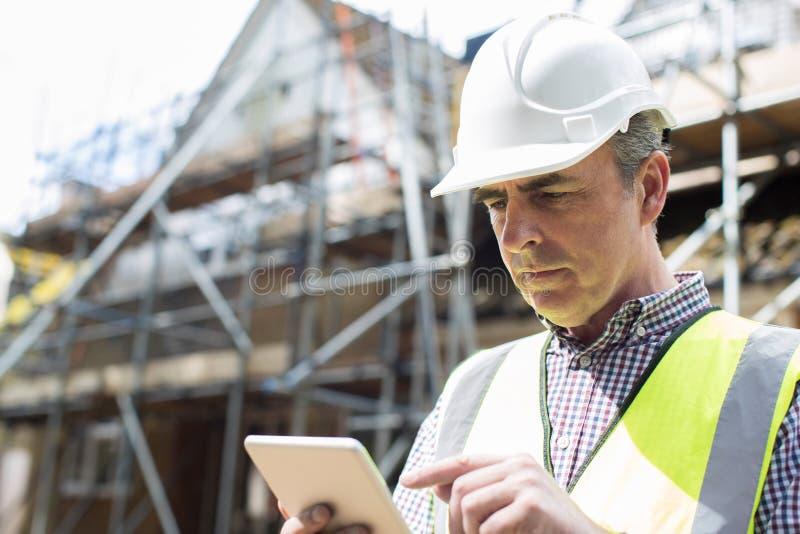 Architecte On Building Site à l'aide de la Tablette de Digital photo stock
