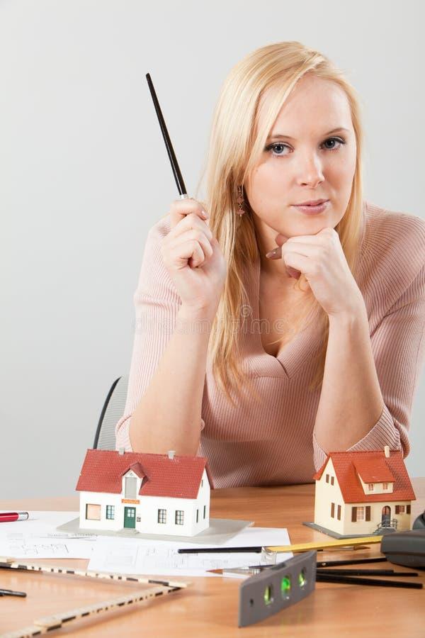 Architecte de femme à sa table de travail exposant la maison photographie stock libre de droits