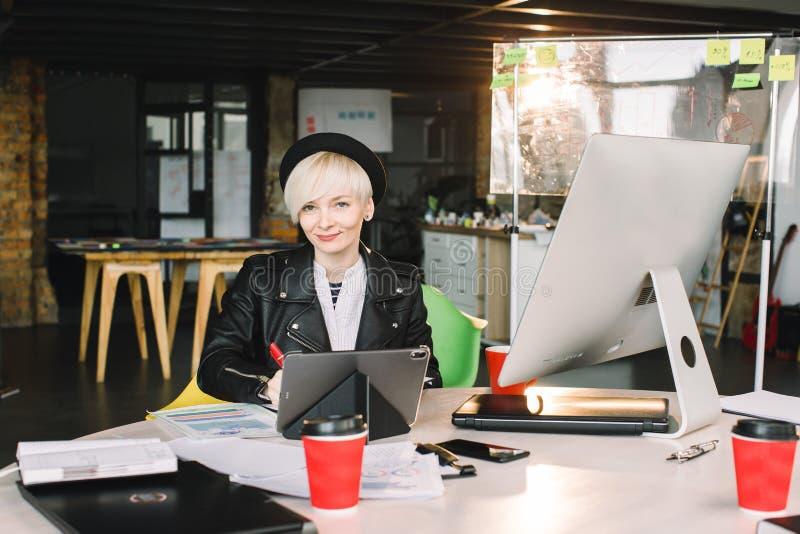 Architecte de jeune femme dans le fonctionnement de chapeau noir et de veste de leasure à la table Photo de femme blonde travaill images stock