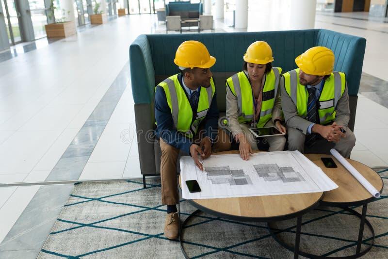 Architecte ethnique multi d'affaires s'asseyant et discutant au-dessus du croquis de mise au point dans le lobby au bureau photographie stock libre de droits