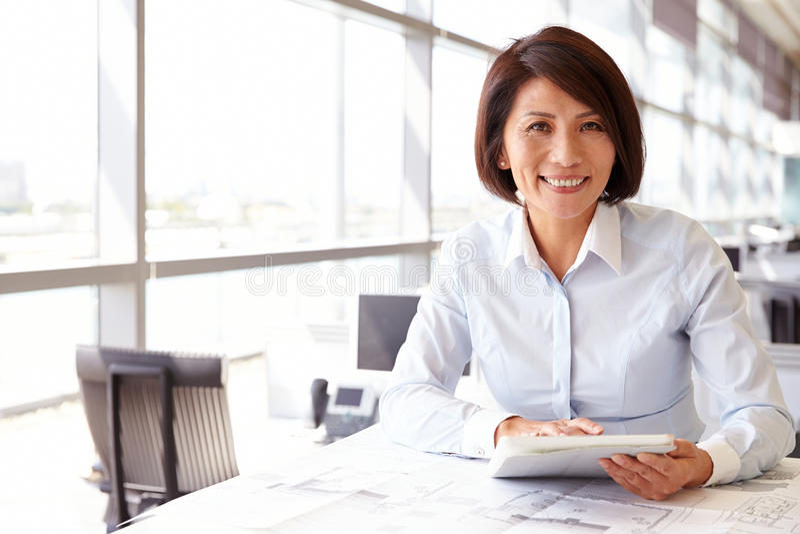 Architecte féminin à l'aide de la tablette, regardant à l'appareil-photo photographie stock libre de droits