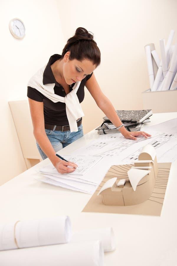 Architecte féminin aux notes d'écriture de bureau photographie stock libre de droits