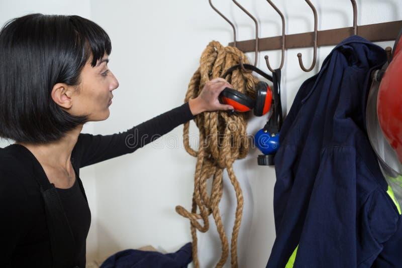 Architecte féminin enlevant le manchon d'oreille du cintre photographie stock libre de droits