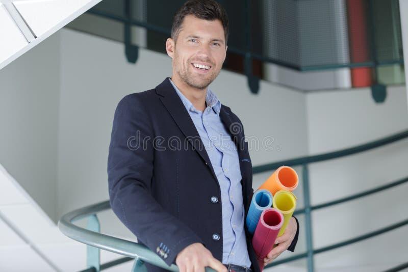 Architecte masculin de sourire tenant des modèles à l'intérieur du bâtiment images libres de droits