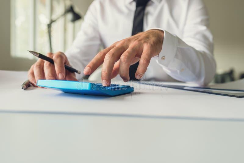 Architecte ou concepteur s'asseyant à son bureau utilisant le calculato image stock