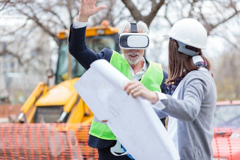 Architecte ou homme d'affaires supérieur employant des lunettes de réalité virtuelle sur un chantier de construction photos libres de droits