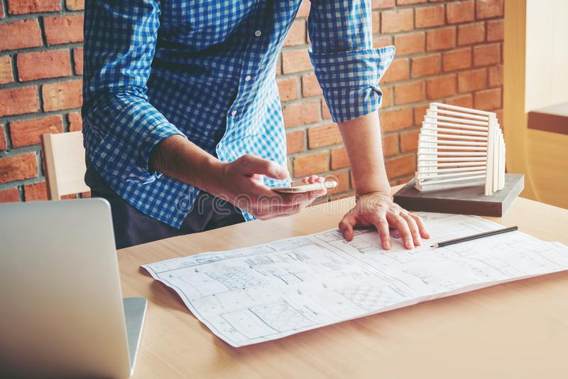 Architecte ou ingénieur à l'aide du téléphone intelligent fonctionnant dans le bureau sur bleu photographie stock libre de droits
