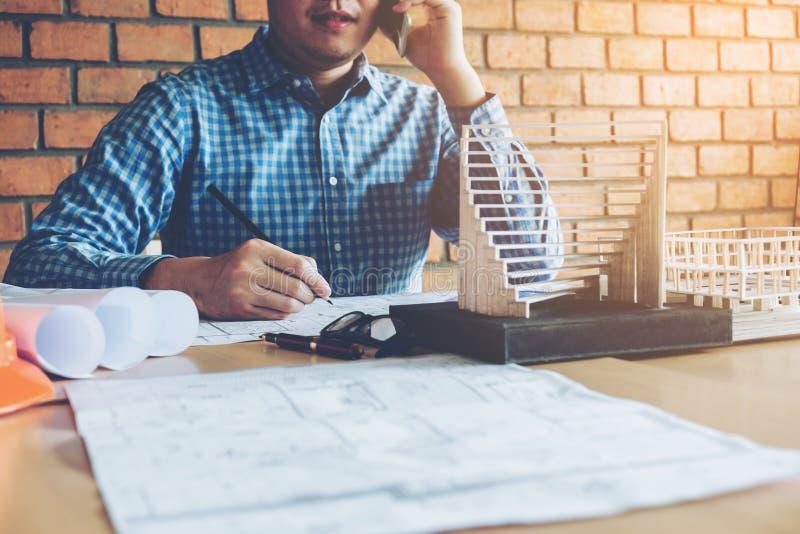 Architecte ou ingénieur à l'aide du téléphone intelligent fonctionnant dans le bureau sur bleu photos stock
