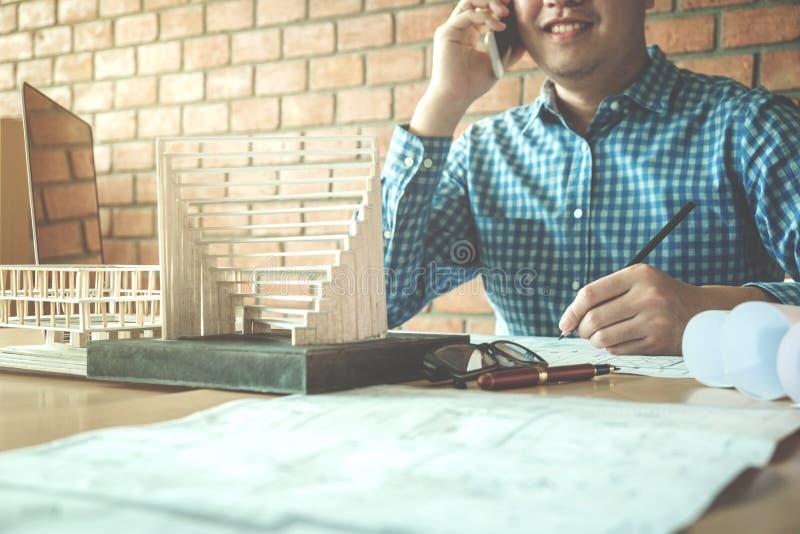 Architecte ou ingénieur à l'aide du téléphone intelligent fonctionnant dans le bureau sur bleu images libres de droits
