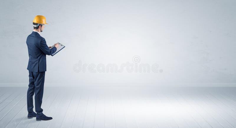 Architecte se tenant dans un espace vide et tenant un plan photographie stock libre de droits