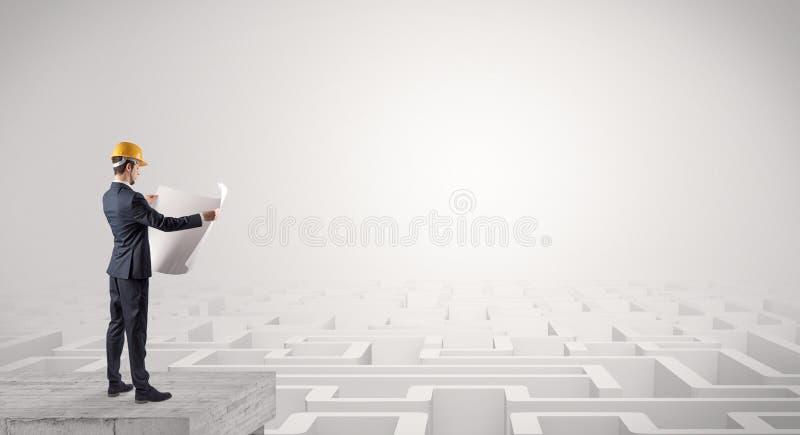 Architecte se tenant sur un labyrinthe et tenant un plan image stock