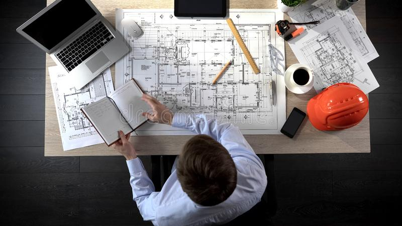 Architecte vérifiant des notes faisant dans son carnet pour l'ajouter au dessin du bâtiment images libres de droits
