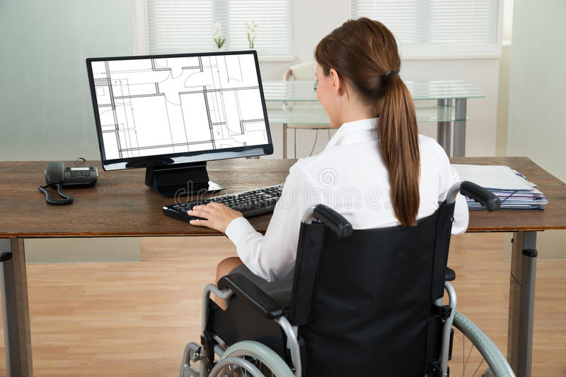 Architecte On Wheelchair Looking au modèle sur l'ordinateur photos libres de droits