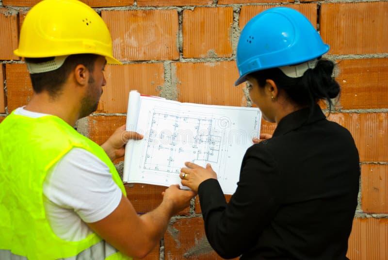 Architecten die en op blauwdrukken werken kijken stock foto's