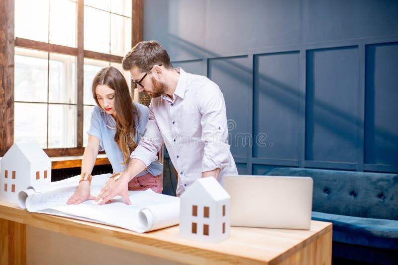 Architecten die in het bureau werken stock afbeelding