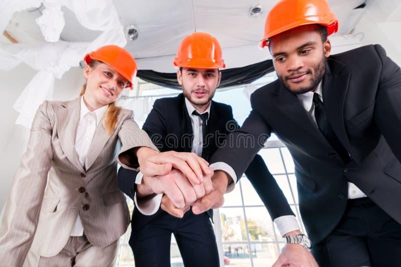 Architecten gelegde handen op handen Drie ontmoete businessmеnarchitect stock afbeeldingen