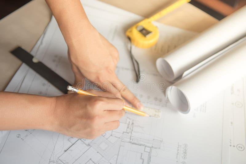 Architecten mannelijke handen die op architecturale tekening schetsen stock afbeeldingen