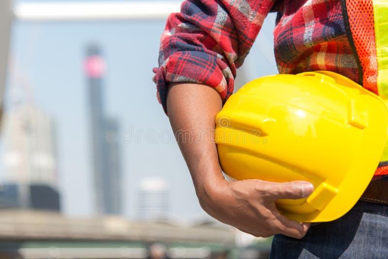 Architectenarbeider die gele helm houden stock fotografie