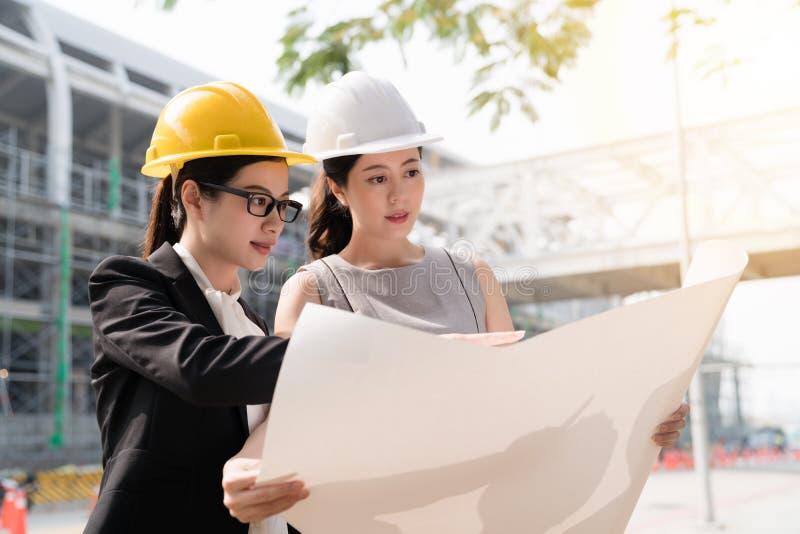 Architectenmeisje die helmat het bekijken het plan dragen royalty-vrije stock fotografie