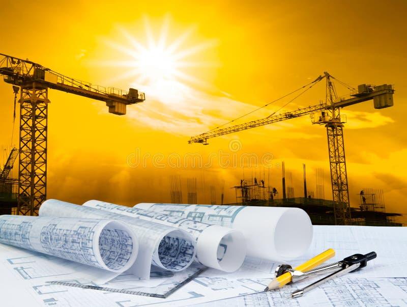Architectenplan op werkende lijst met kraan en bouwconstructieachtergrond stock foto