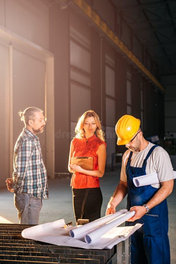 Architectenteam die blauwdruk controleren op het werkplaats stock afbeelding