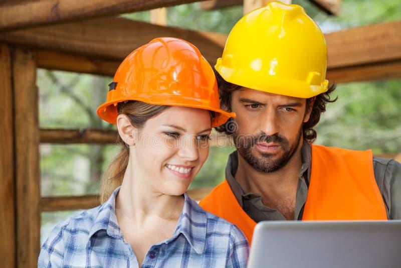 Architectes à l'aide de l'ordinateur portable au chantier de construction images libres de droits