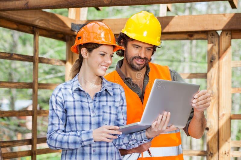 Architectes travaillant sur l'ordinateur portable au chantier de construction photographie stock libre de droits