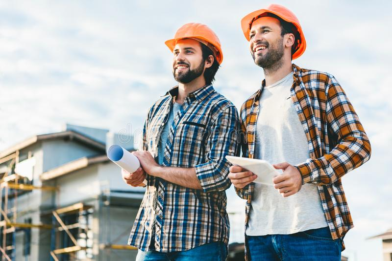 Architects with blueprint and tablet looking away. At construction site stock photos