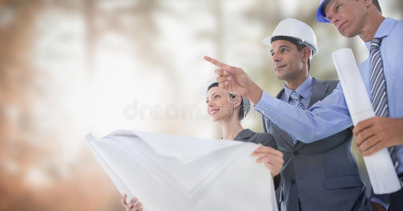 Architects with blueprints on building site. Digital composite of Architects with blueprints on building site stock photos