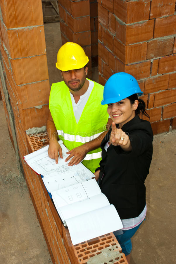 Architects with blueprints pointing up royalty free stock image