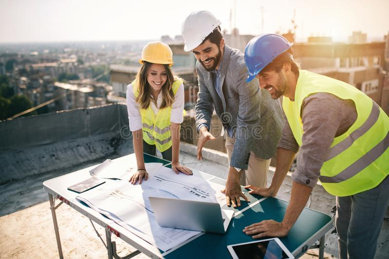 Architects, business manager and engineer meeting project at building site. Architects, business manager and engineer meeting project at construction site stock photo
