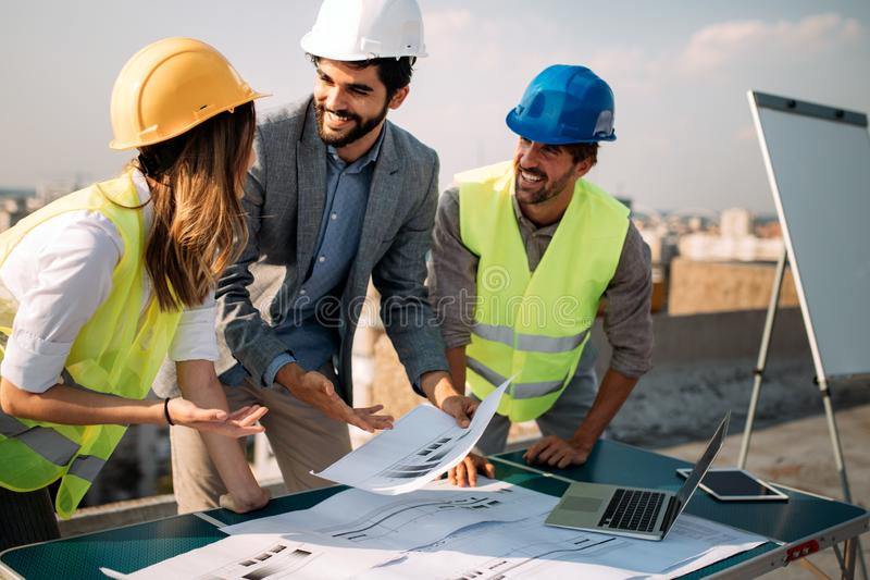 Architects, business manager and engineer meeting project at building site. Architects, business manager and engineer meeting project at construction site royalty free stock photo