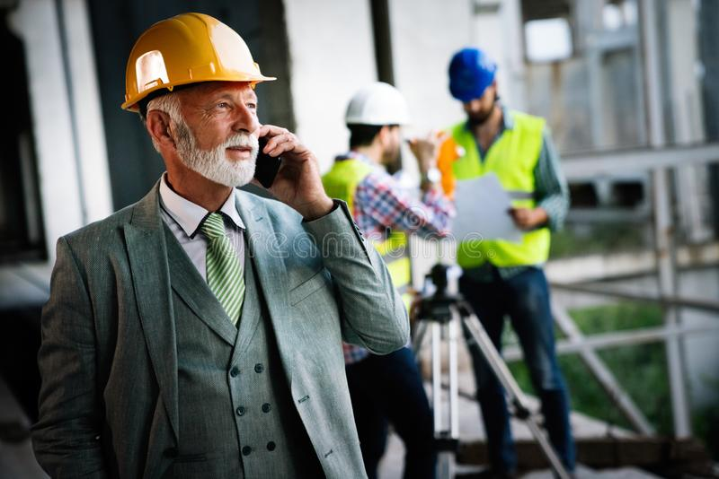 Architects, business manager and engineer meeting project at construction site royalty free stock image