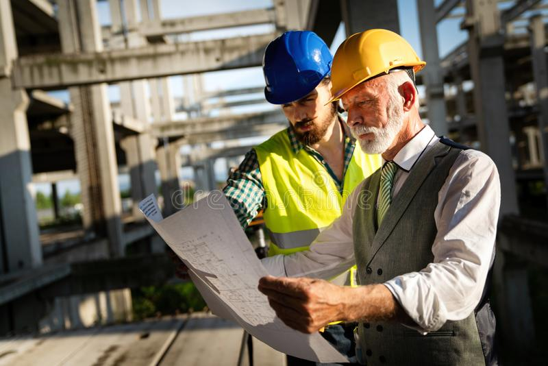 Architect and construction engineer or surveyor discussion plans and blueprints stock photography